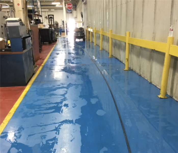 Commercial warehouse facility with blue flooring pooled with water after a loss.