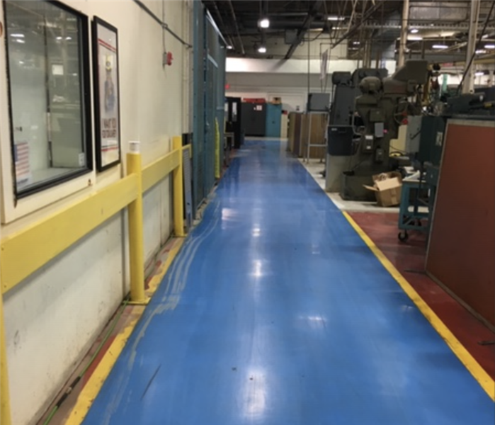 Commercial warehouse facility with blue flooring after water was extracted.