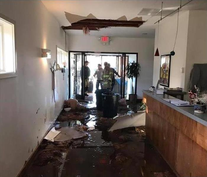 Hole on ceiling, ceiling tiles on floor, standing water on floor, firefighters on entrance door