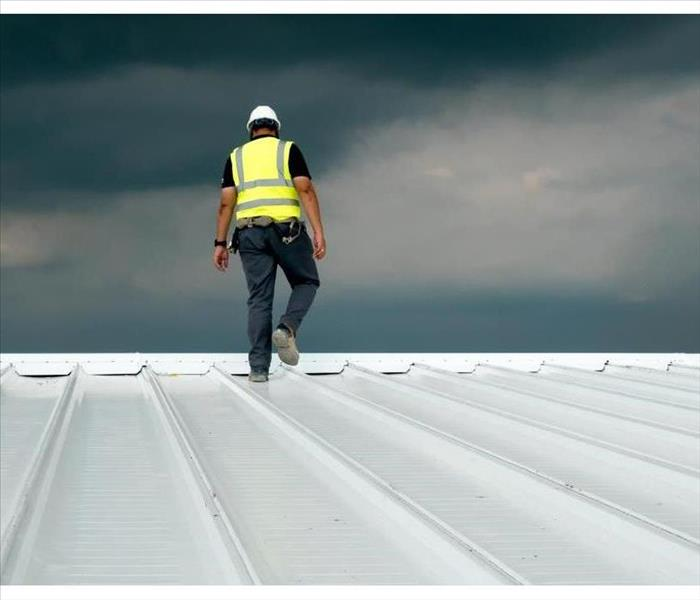 Construction engineer wearing safety uniform inspection metal roofing work for roof industrial concept with copy space