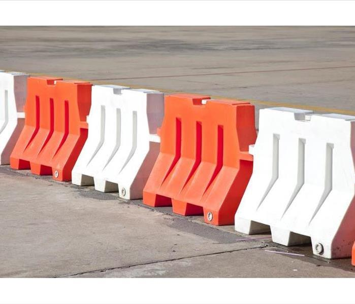 Red and white plastic barriers blocking the road