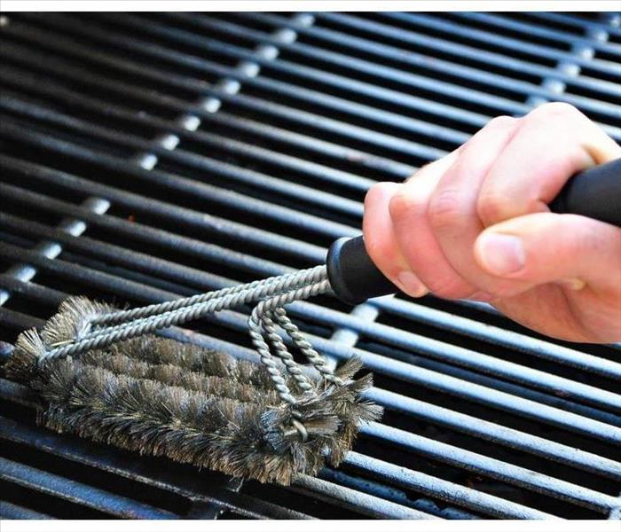 Cleaning a grill at a summer barbecue party.