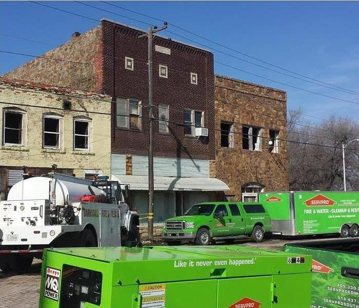 Servpro vehicles parked in front of a building that has had fire damage